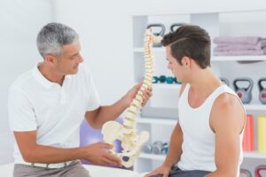 Chiropractor showing the spine to a guest a Bolton Spinal Health